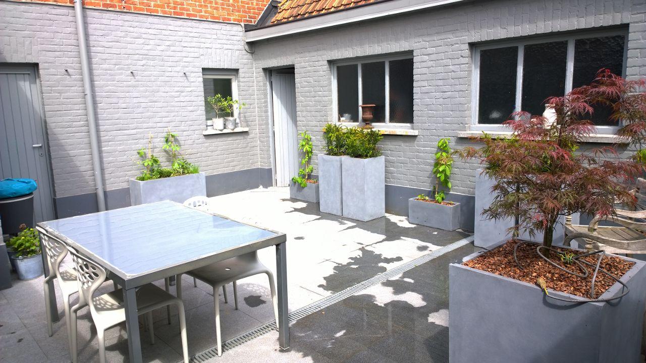 Tuinontwerp Izegem - Binnentuin afgewerkt met polystone bloembakken